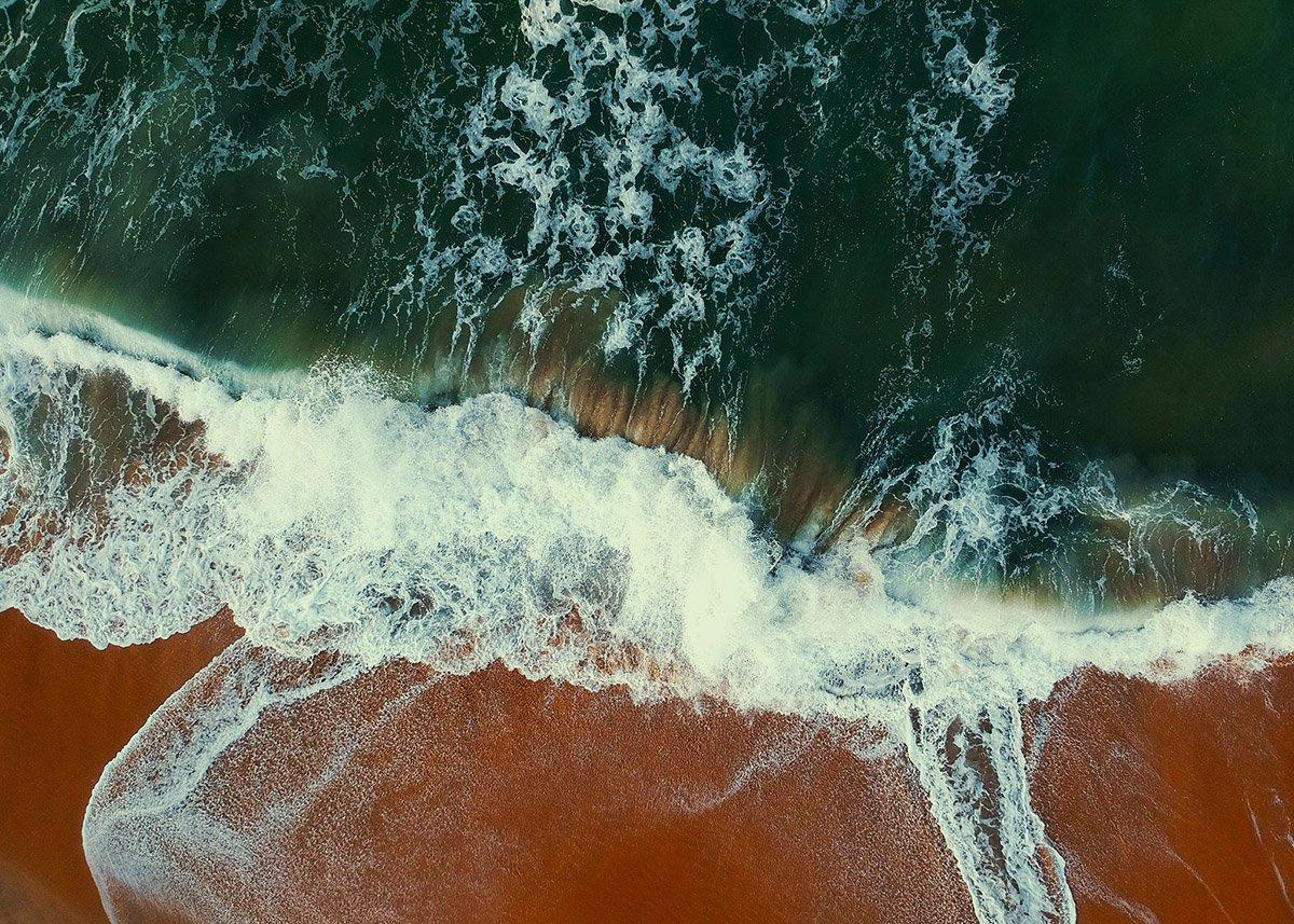 Vågor sveper in över en sandstrand